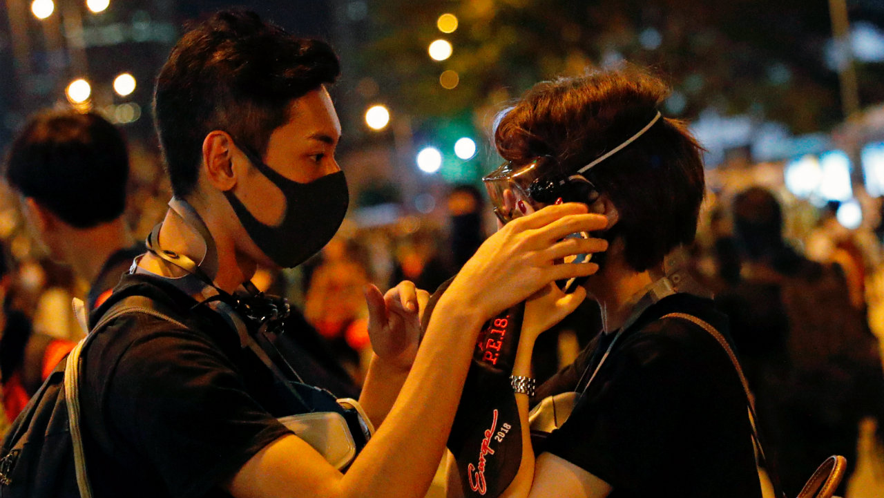 An anti-extradition bill protester helps his girlfriend adjust a gas mask during a march in Hong Kong on August 18. This was the 11th consecutive weekend of protest. (Image: Reuters)
