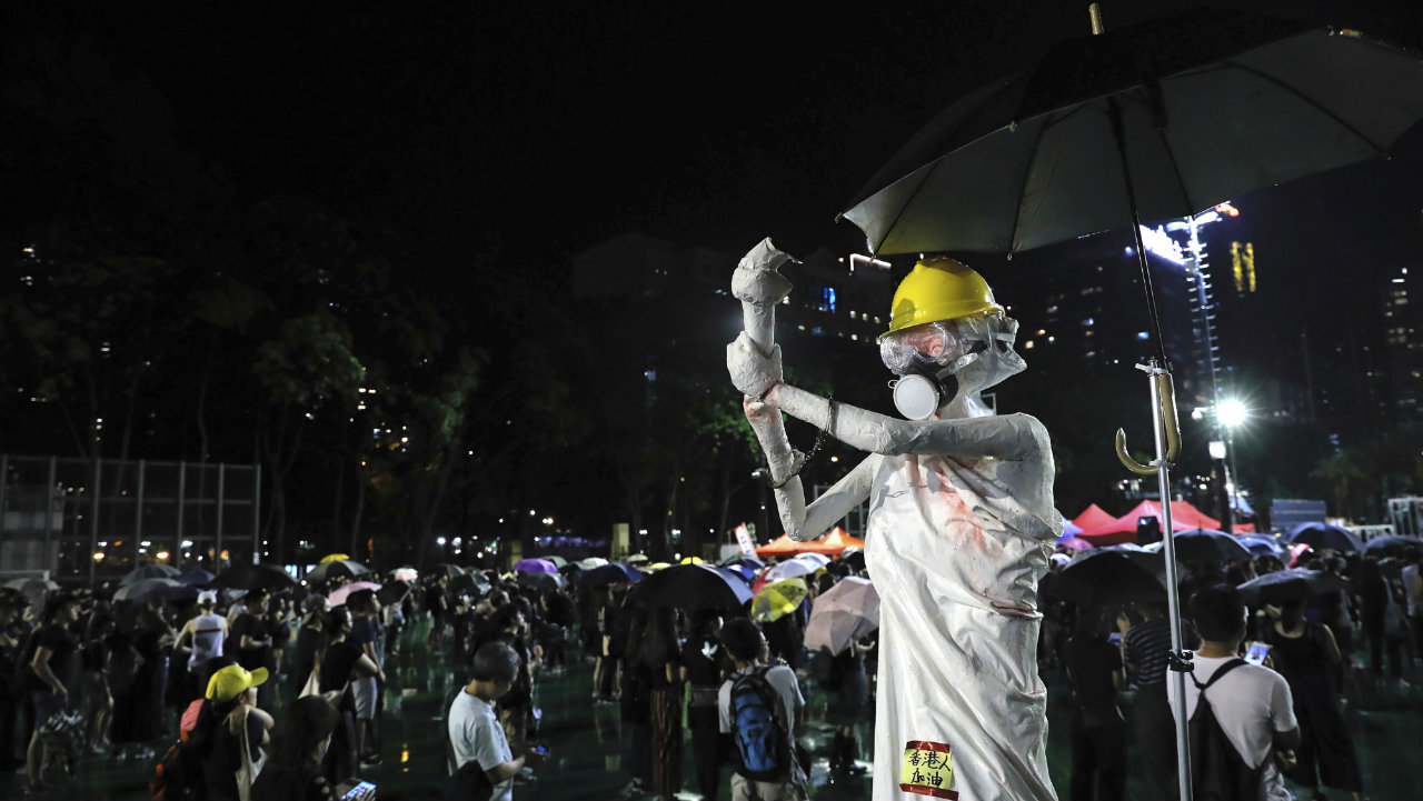 Demonstrators gather near a replica of the 'Goddess of Democracy' statue wearing a hard hat, gas mask, handcuffs and covered in a red liquid in Hong Kong. Goddess of Democracy was a 10-metre-tall statue created during Beijing's Tiananmen Square protests of 1989. (Image: AP)