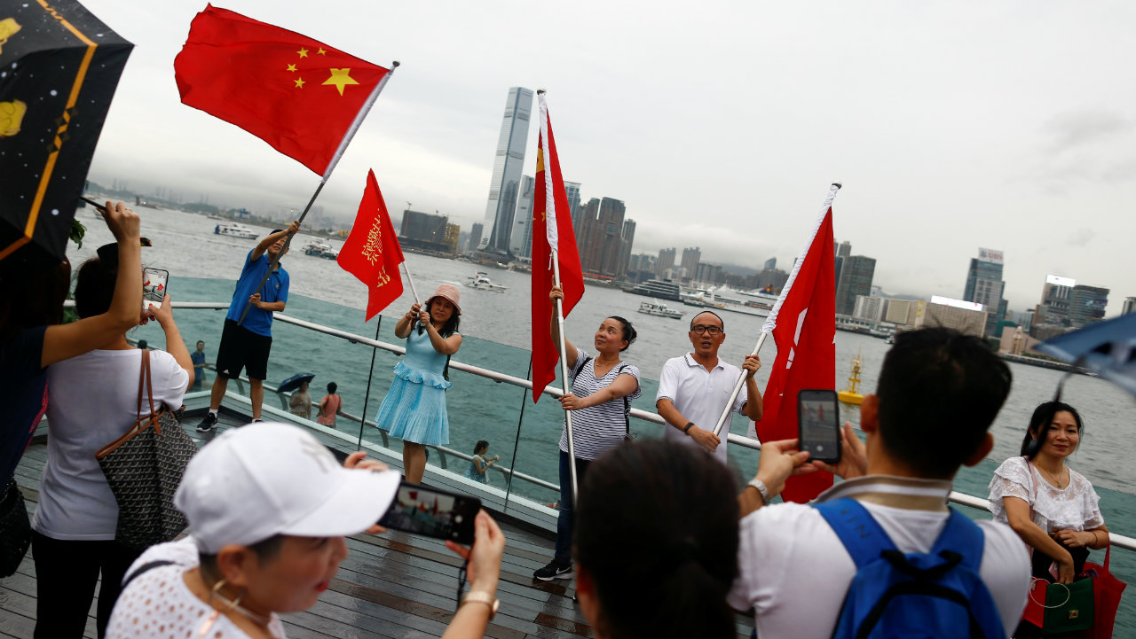 "People hold Chinese and Hong Kong flags at the pro-China ""Safeguard Hong Kong"" rally at Tamar Park to voice support for the police in Hong Kong on August 17, 2019. (Image: Reuters)"