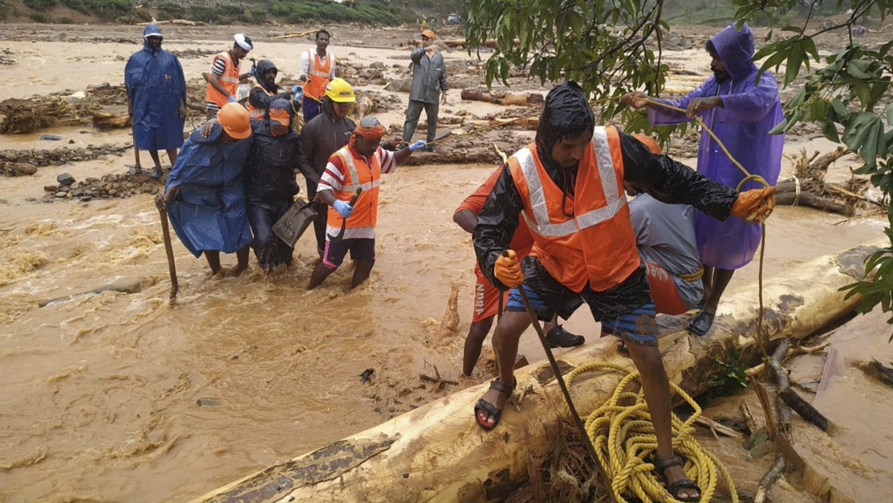 National Disaster Response Force (NDRF) personnel help move flood victims to safer areas in Kerala's Wayanad district. Dozens of people have died and some 1 lakh moved to relief camps following flash floods and mudslides caused by days of torrential rains in the southern state. (Image: NDRF handout via AP)
