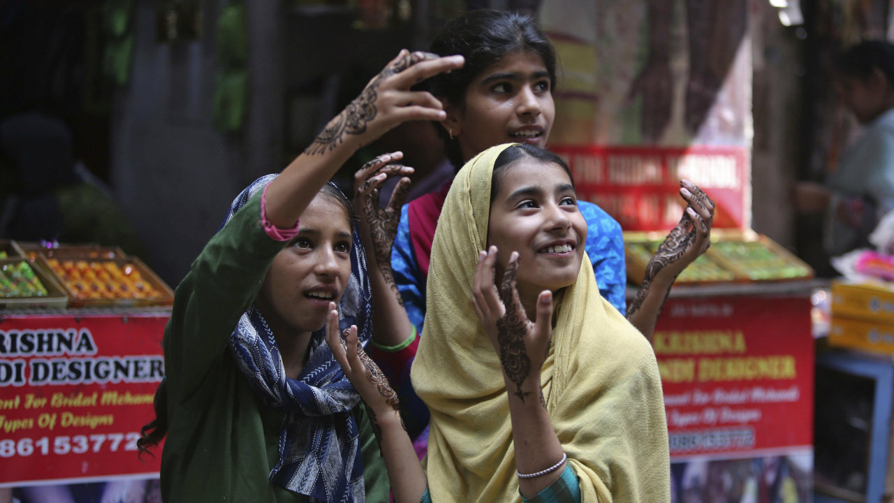 Girls gesture after getting henna decorations on their hands on the eve of Eid al Adha, in Jammu, Jammu and Kashmir. (Image: AP)