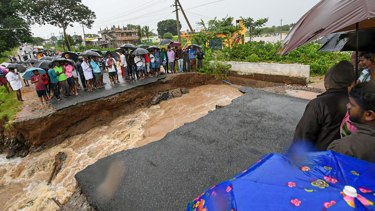 Locals stranded as a part of the road collapsed after water from Kabini reservoir in HD Kote was released following heavy monsoon rainfall, in Mysore. (Image: PTI)