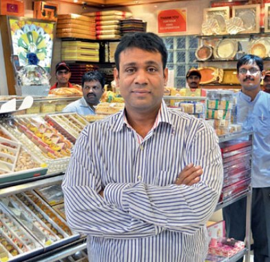 Q7. He spent his initial years in Bangalore before moving to Hyderabad. He started his first shop in Himayatnagar in 1993 with Rs 30,000 in seed capital and blessings and expertise from his mother. Identify him