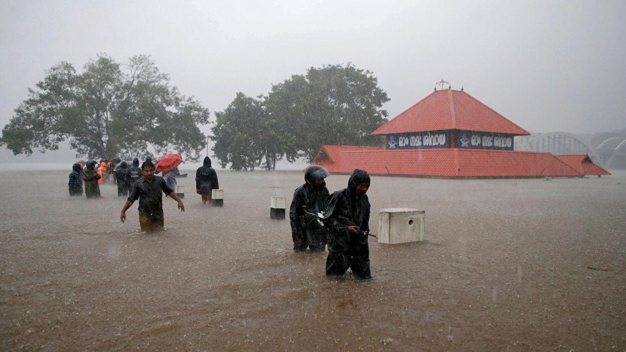 Members of a rescue team wade through a water-logged area past a submerged temple during heavy rains on the outskirts of Kochi in Kerala. (Image: Reuters)