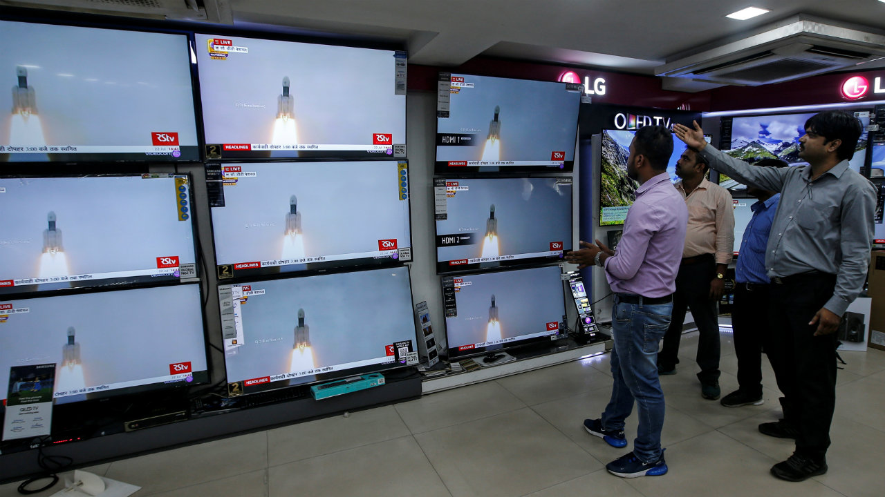 People celebrate as they watch the live broadcast of Chandrayaan 2's launch, inside an electronics showroom in Kolkata, India. (Image: Reuters)