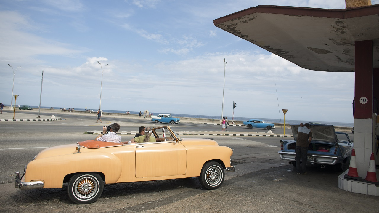 "Cuba | Cost per litre – Rs 6.38 | A tourist takes a photograph from the back of a vintage car whilst waiting in line to fill up with fuel at a gas station along the seafront boulevard ""El Malecon"" in Havana. (Image: Reuters)"