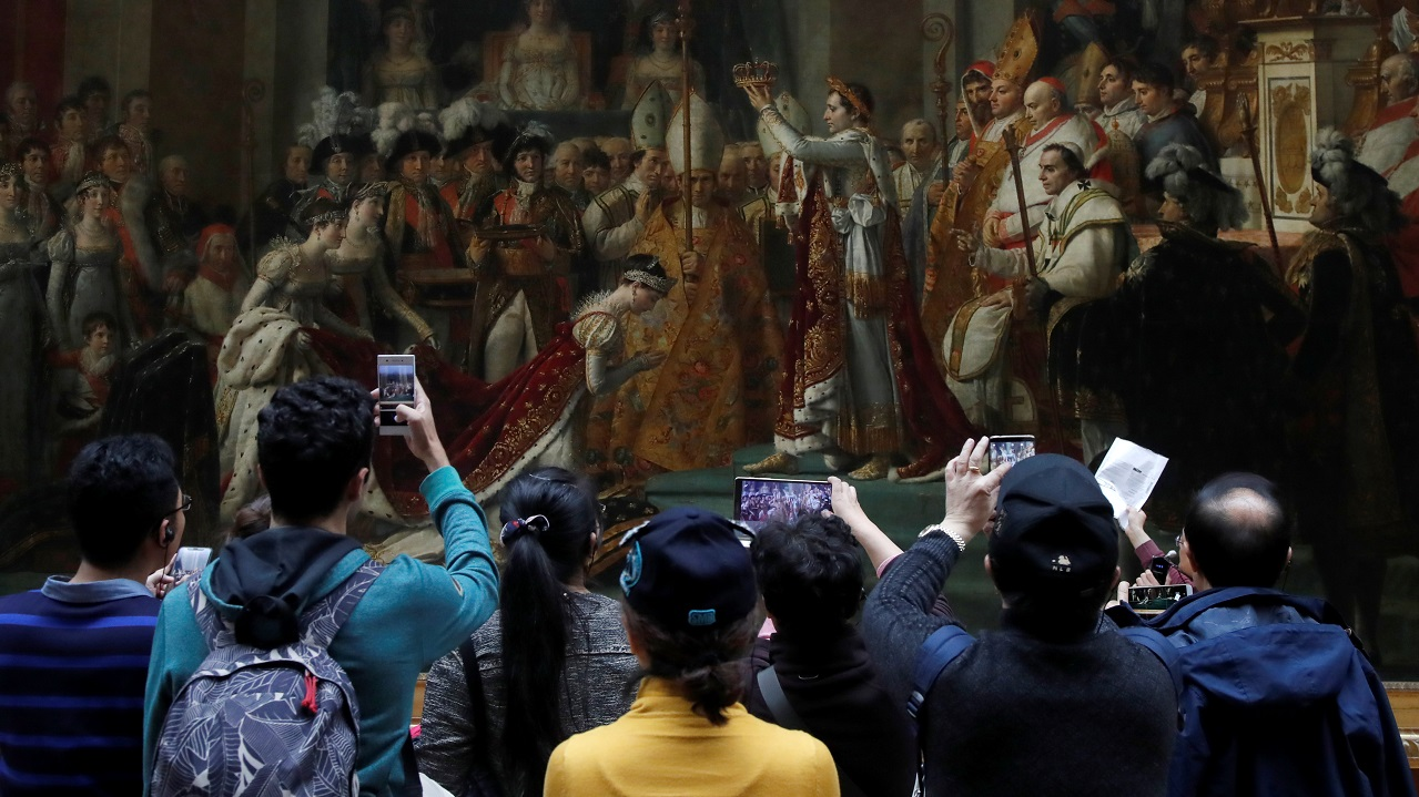 Visitors look at the Coronation of Napoleon, a 1806 painting by Jacques Louis David at the Louvre museum in Paris, France, December 3, 2018. Picture taken December 3, 2018. REUTERS/Charles Platiau - RC1555FCE100