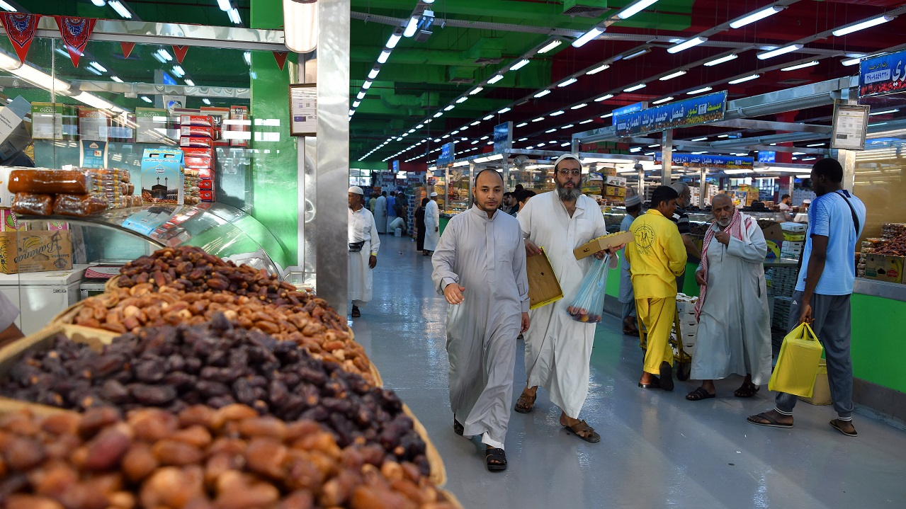 People walk near dates stands in a food and dates market in Mecca, Saudi Arabia, August 7, 2019. Picture taken August 7, 2019. REUTERS/Waleed Ali - RC1831720800