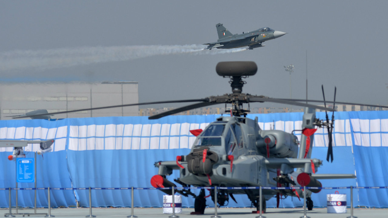 IAF's Tejas aircraft performs as an Apache helicopter is seen parked in the foreground. (Image: PTI)