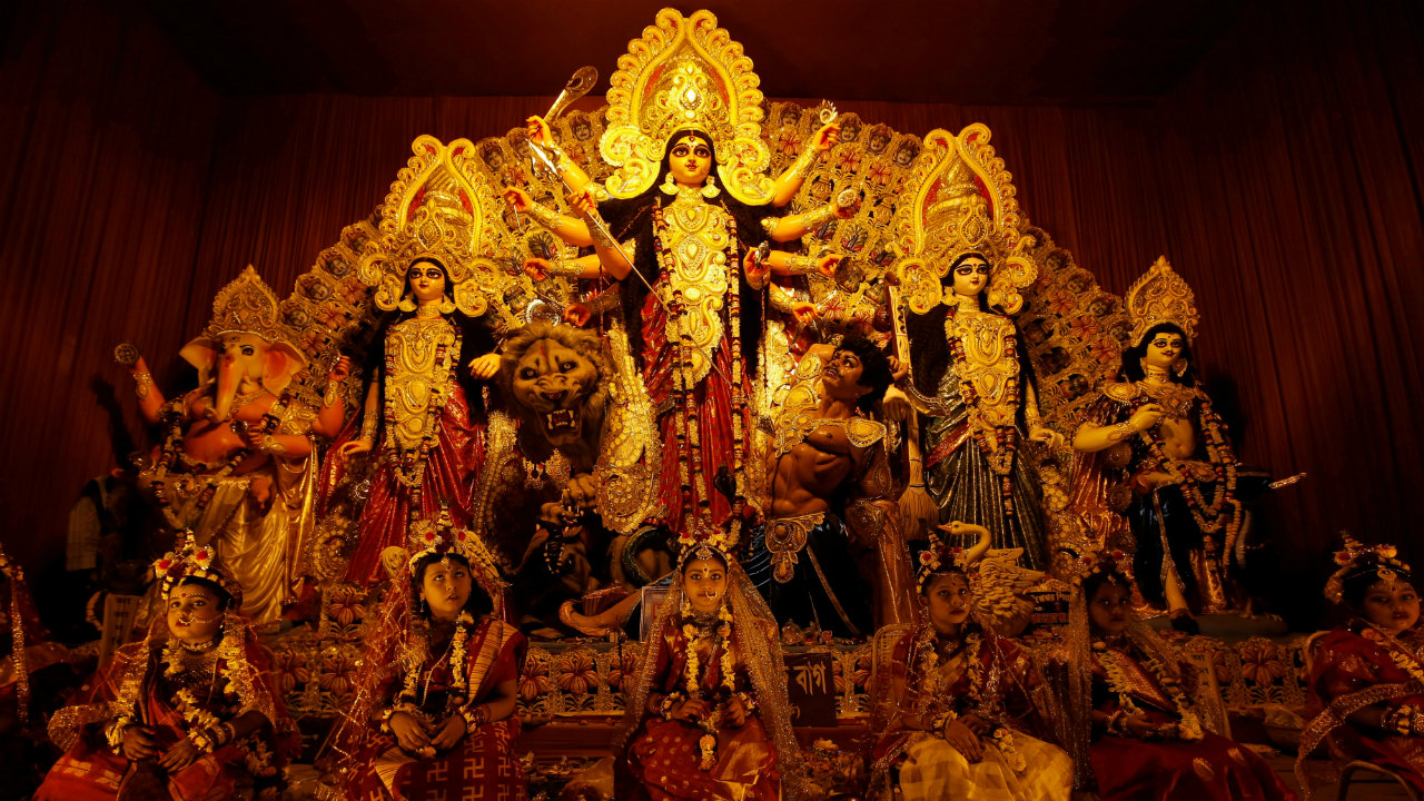 Young girls dressed as Kumari sit in front of the idols of Hindu goddess Durga before being worshipped as part of a ritual during the Durga Puja festival celebrations at a pandal in Kolkata (Image: Reuters)