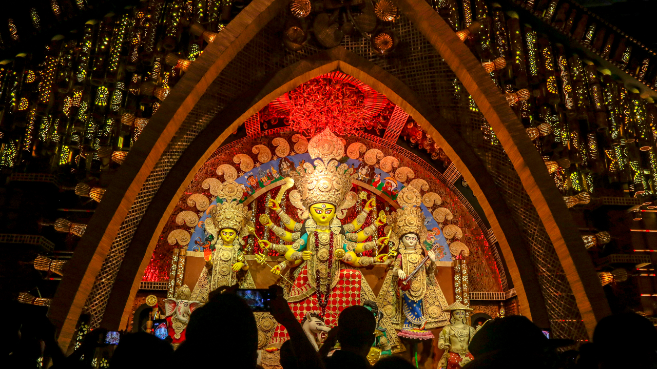 """Devotees throng inside a """"pandal,"""" or a temporary structure set up to worship Hindu goddess Durga during the Durga Puja festival in Kolkata, (Image: AP)"""