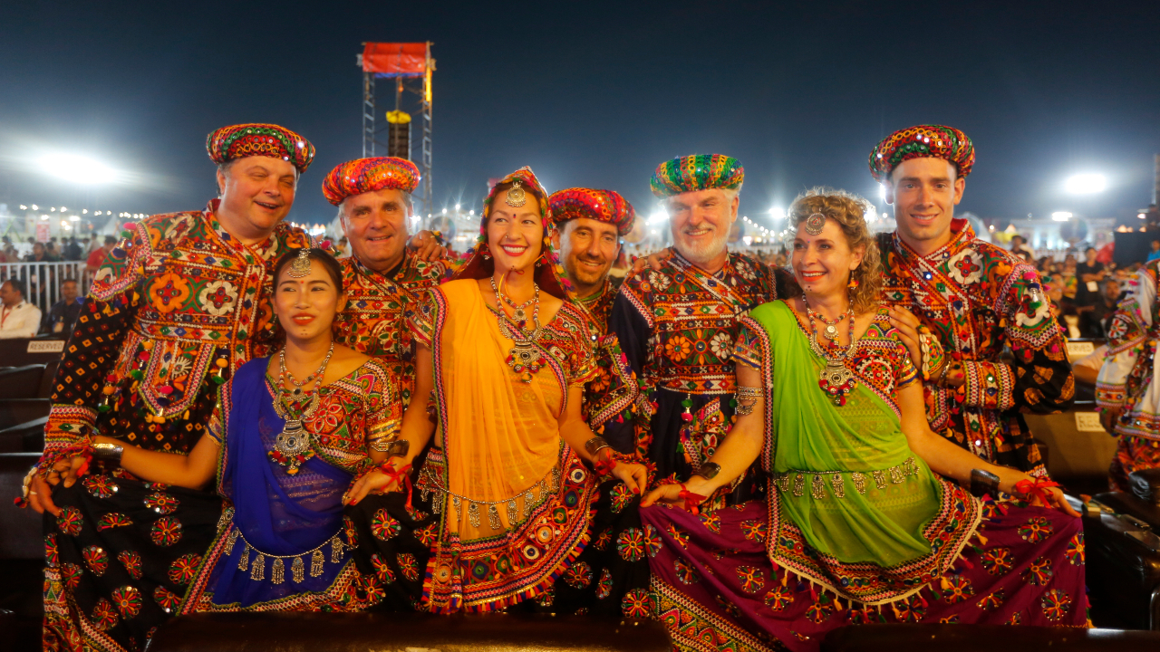 Foreigners wearing Indian traditional attire pose for photograph during an inauguration function for the Hindu festival Navratri in Ahmadabad. (Image: AP)