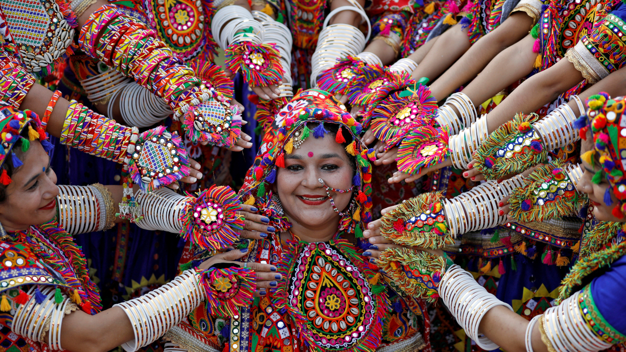 Participants dressed in traditional attire pose for pictures during rehearsals for Garba, a folk dance, in preparations for Navratri, a festival during which devotees worship the Hindu goddess Durga, in Ahmedabad. (Image: Reuters)