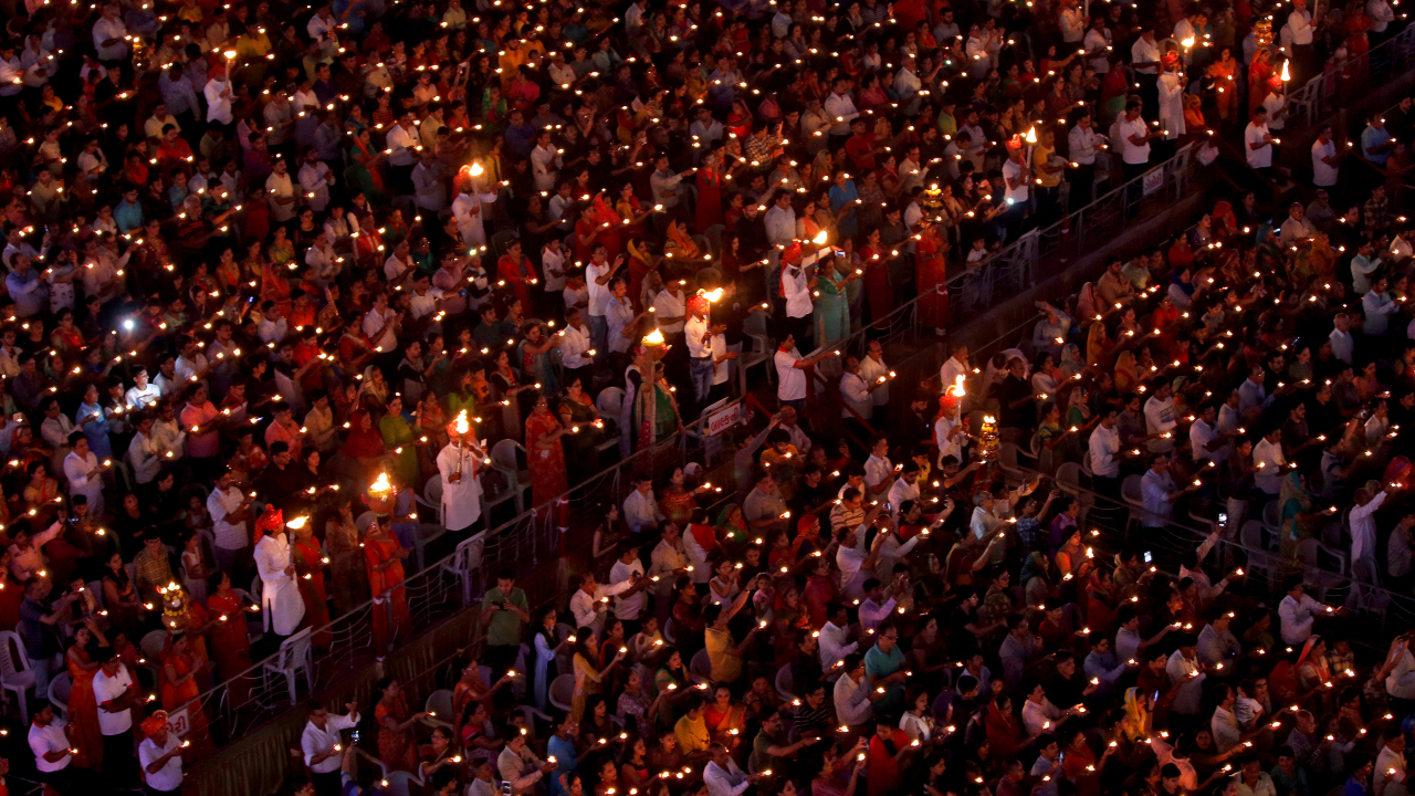 """Hindu devotees hold earthen lamps and torches to perform prayers called """"Aarti"""" during the celebrations to mark the Navratri festival, in which devotees worship Hindu goddess Durga, at Surat in Gujarat. (Image: Reuters)"""