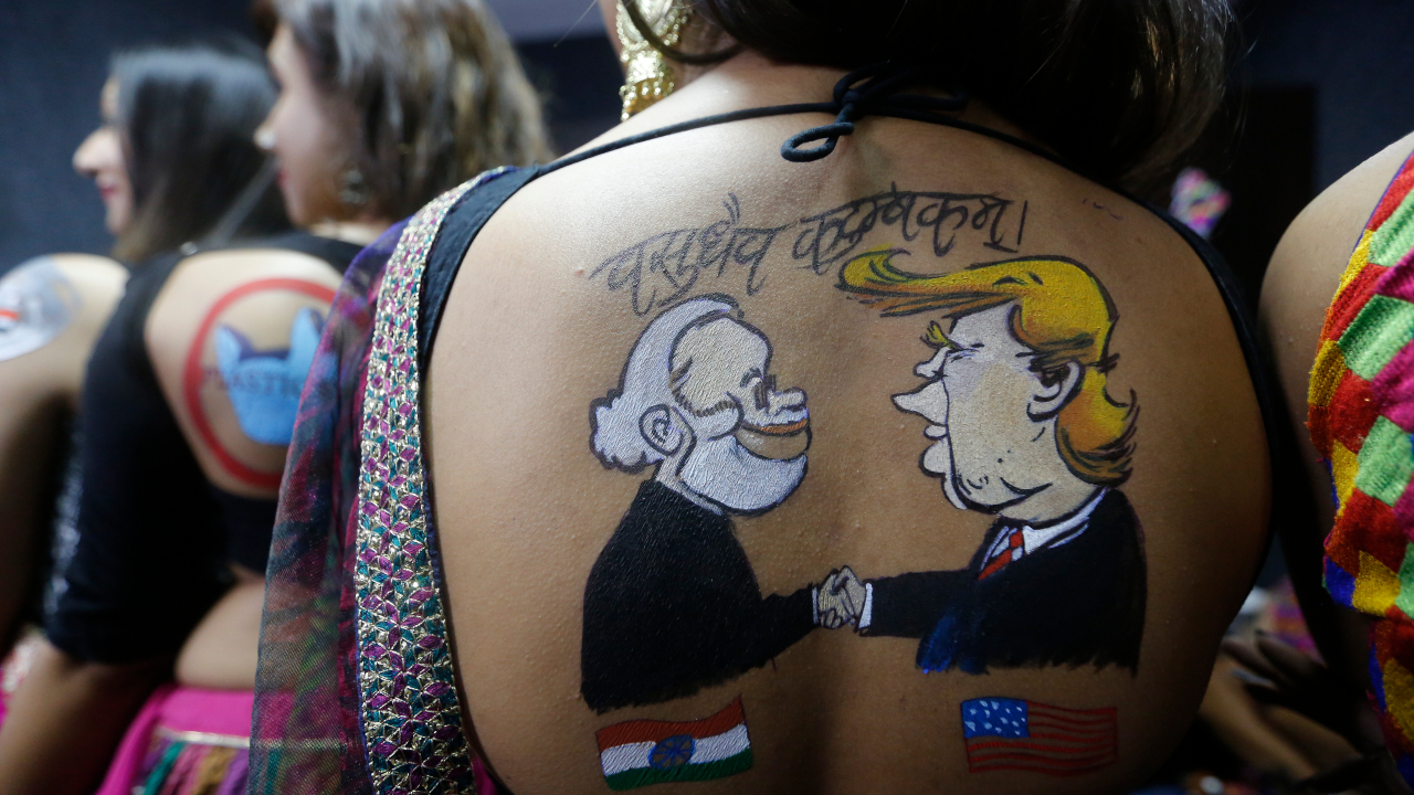 """An Indian girl displays a tattoo depicting Indian Prime Minister Narendra Modi and President Donald Trump, done on her back in preparation of forthcoming Hindu festival Navratri in Ahmadabad. The Hindu festival of Navratri or nine nights began from Sept. 29. Gujarati reads, """"the world is one family"""". (Image: AP)"""