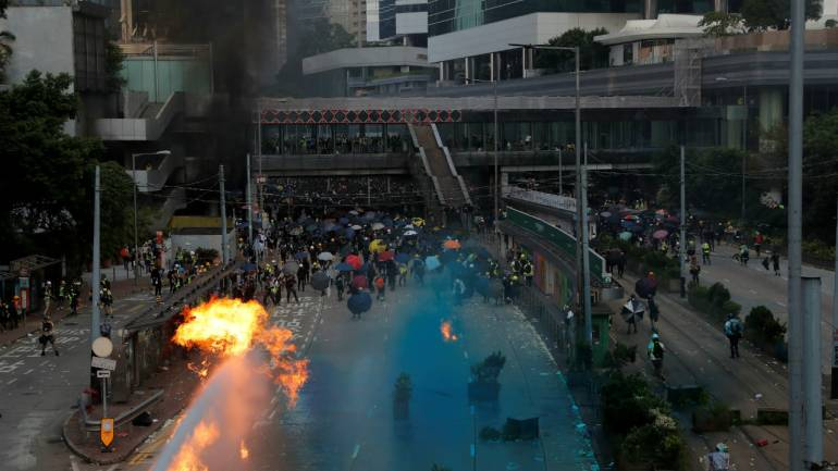 Hong Kong police fire water cannon, tear gas as protests spread