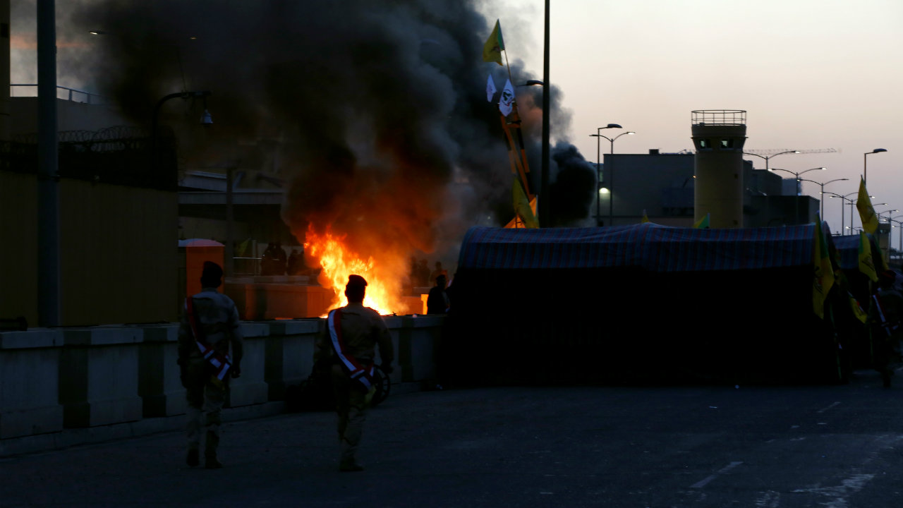 Iraqi security forces walk as the Hashd al-Shaabi (paramilitary forces) fighters set the U.S. Embassy wall on fire, as they protest to condemn air strikes on their bases, in Baghdad, Iraq December 31. (Image: Reuters)
