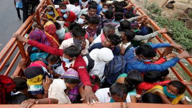 Migrant workers and their families on board a truck are returning to their villages after the 21-day nationwide lockdown was announced, in Ahmedabad, March 25. REUTERS